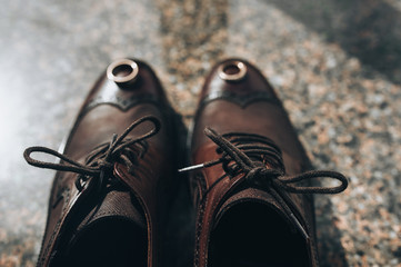 Tied shoelaces, wedding gold rings on brown leather shoes of the groom close-up. Photography, concept, top view.