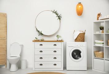 Interior of stylish bathroom with washing machine