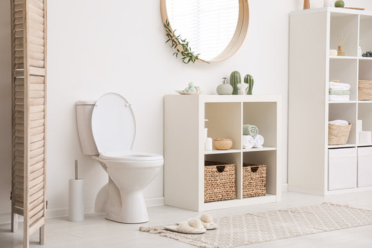 Modern toilet bowl near white wall in bathroom