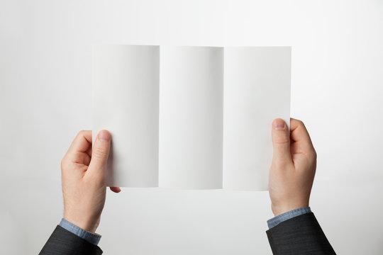 Tri-fold paper brochure in hands. Z-fold design blank for marketing or advertising.
