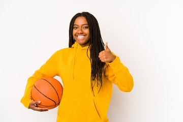 Young african american woman playing basketball isolated smiling and raising thumb up