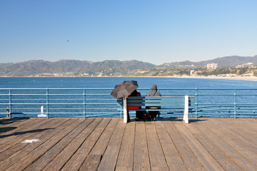 An anonymous couple sit on a bench on the Santa Monica pier.