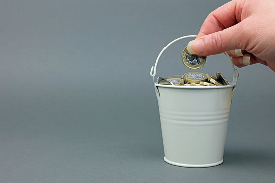 A hand adding a pound coin to a bucket full of cash.