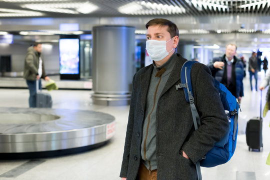 Young European man in gray coat, protective disposable medical mask in airport. Afraid of dangerous N-CoV 2019 influenza coronavirus mutated and spreading in China. Blue backpack, suitcase on wheels