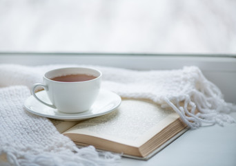 Foto op Plexiglas Thee Warm knitted scarf, a cup of hot tea and a book