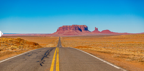 Panoramic picture of endless road in front of majestic rock formation in the Monument Valley National park in winter