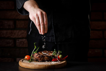 The concept of cooking meat. The chef cook salt on the cooked steak on a black background, a place under the logo for the restaurant menu. food background image, copy space text