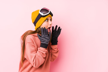 Young caucasian woman wearing a ski clothes isolated shouts loud, keeps eyes opened and hands tense.