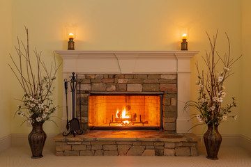 Cozy fire in a stone fireplace in a residential home with candles and flowers.