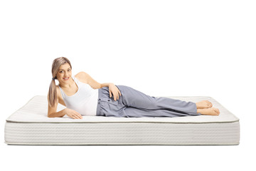 Young woman lying on a bed mattress in pajamas and smiling at the camera