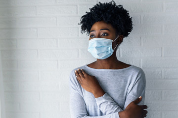 Portrait of young African-American woman wearing disposable medical face mask Fotoväggar