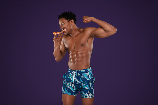 Fit african man eating pizza.