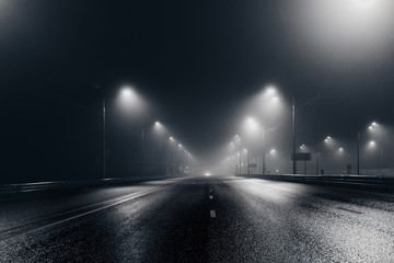 Spoed Fotobehang Nacht snelweg Foggy misty night road illuminated by street lights