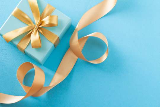 青いギフトボックスと金色のリボンのプレゼントのイメージ