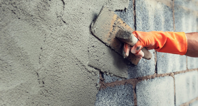 close up hand worker plastering cement on wall for building house