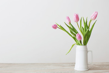 pink tulips in white ceramic jug on wooden table on background white wall Fototapete