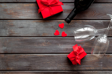 Valentines Day concept with wine, glasses, red present box on dark wooden background top-down copy space
