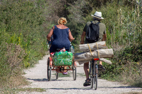Rear View Of Man And Woman Riding Bicycles On Dirt Road