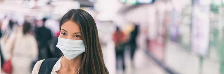 Coronavirus corona virus Asian woman wearing flu mask walking on work commute in public space transport train station or airport panoramic banner.