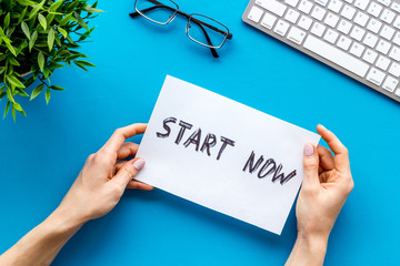 Start now. Motivative text on blue office desk top-down