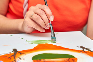 Foto op Aluminium Koraal Artist paints landscape in gouache using a brush. Woman's hand is holding brush. Closeup, selective focus