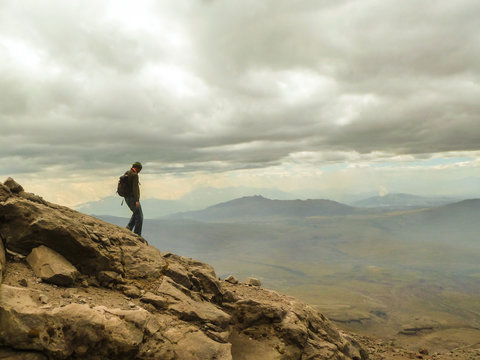 Man Standing On Rock At Mountain Against Cloudy Sky