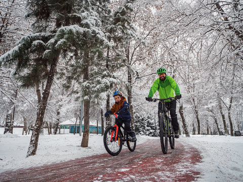 Man and his son ride bicycles along a bicycle path in a winter park. Father and son spend an active weekend in the park
