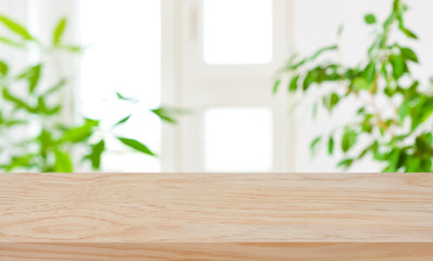 Wood table top on blur window and green plants background