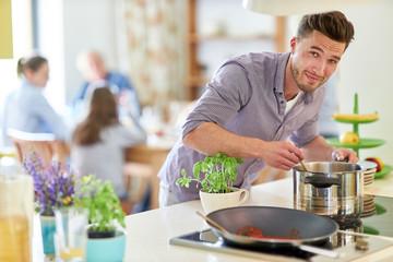 Mann als Hausmann und Hobbykoch beim kochen Wall mural