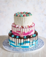 Three-tiered colored cake with colored smudges of chocolate on a light background. Picture for a menu or a confectionery catalog, the wedding cake