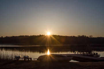 Sunrise on the lake in spring. Boats silhouettes and the rays of the rising sun.