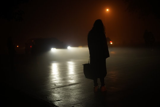 Rear View Of Woman Standing On Road At Night