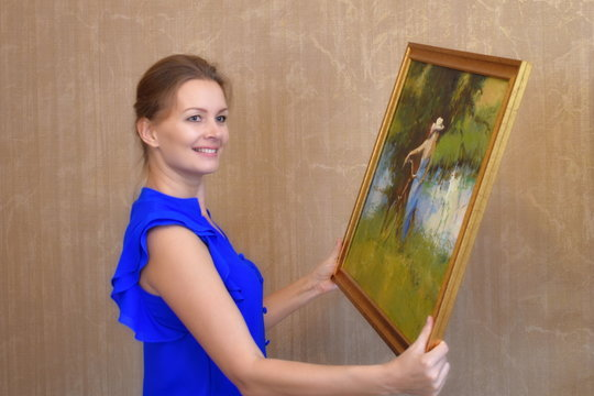 A woman holds a picture in his hand. Karina oil on the wall in the room. Interior decoration landscape painting.