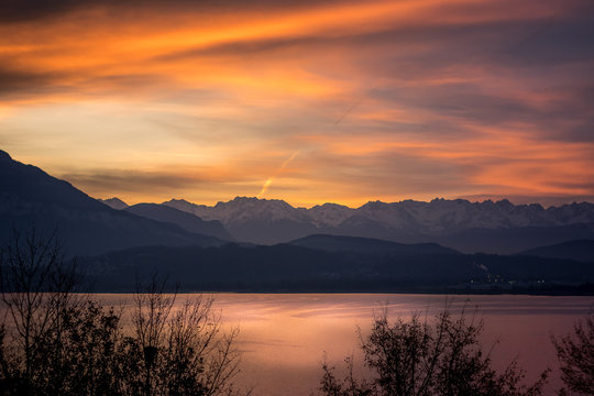 SCENIC VIEW OF LAKE AND MOUNTAINS AGAINST ORANGE SKY