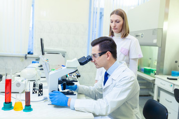 Fototapeta Scientist carries out scientific research looking through microscope in a medical laboratory. Scientist with an assistant.
