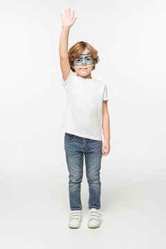 full length view of smiling boy with batman mask painted on face standing with raised hand on white background