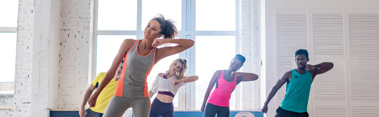 Photo sur Aluminium Pain Panoramic shot of african american trainer and young multiethnic dancers practicing zumba in dance studio