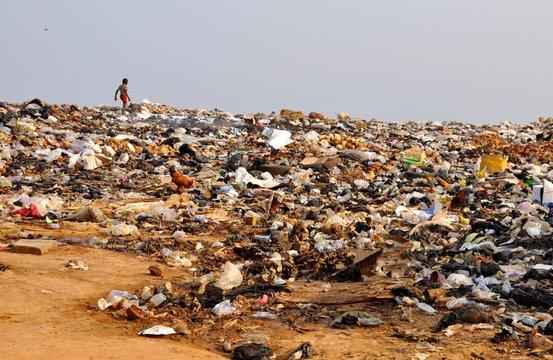 Boy Walking In Garbage Dump Against Clear Sky