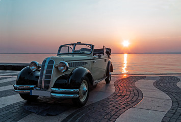 Vintage car near lake at sunset
