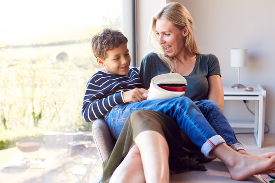 Mother And Son Relaxing In Chair By Window At Home Reading Book Together