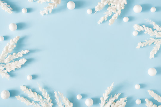 Creative winter nature layout made with snowy branches against pastel blue background. Minimal Christmas background flat lay.