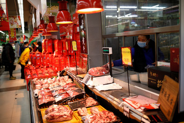 A worker wearing a face mask grabs a piece of meat from the scale at a supermarket, as the country is hit by an outbreak of the new coronavirus, in Beijing