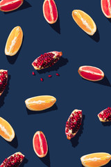 Flat lay pattern with summer citrus fruit on blue background. Minimal concept with sharp shadows. Trendy social mockup or wallpaper.