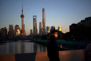 A man wearing a face mask walks on a bridge in front of the financial district of Pudong in Shanghai