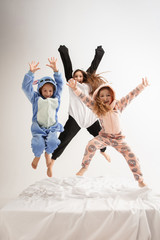 Children in soft warm pajamas colored bright playing at home. Little girls having fun, party, laughting, jumping together, look stylish and happy. Concept of childhood, leisure activity, happiness.
