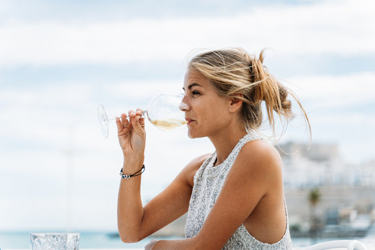 Girl drinking wine from a glass sitting on a restaurant