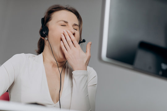 Call center operator is tired of talking to people asking stupid questions. Young customer service representative at work. Young female worker productively operating at call-centre.