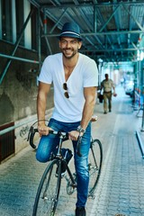Trendy hipster guy riding on bicycle on street