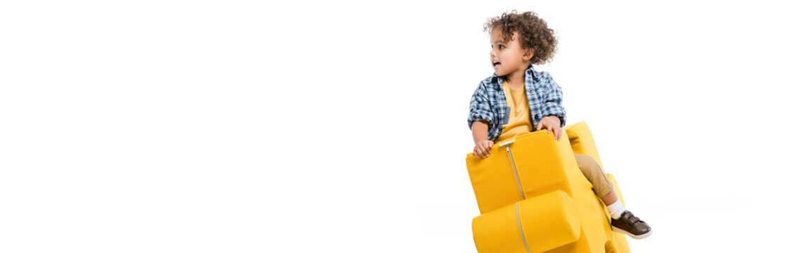 panoramic shot of little african american boy sitting on yellow puzzle chair, isolated on white