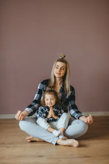 Young woman sitting on the floor in a living room with her little daughter in a lotus pose with closed eyes.